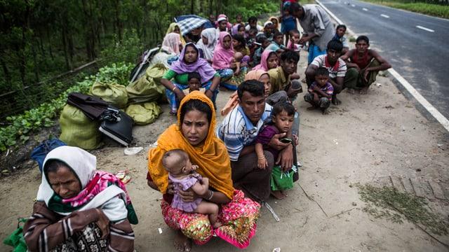 Frauen und Männer mit Kindern sitzen am Strassenrand
