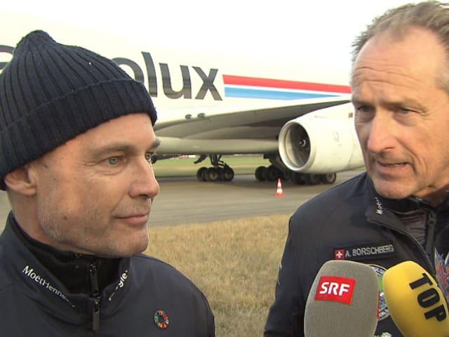 Zwei Männer vor einem Transportflugzeug. Den beiden werden Mikrofone hingehalten.