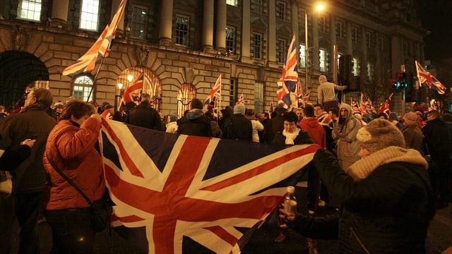 Demonstranten bei Nacht mit Union Jack.