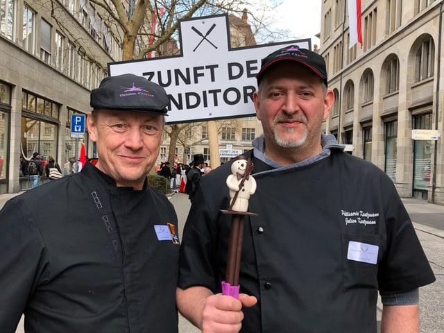 Zwei Männer in schwarzen Kleidern posieren.