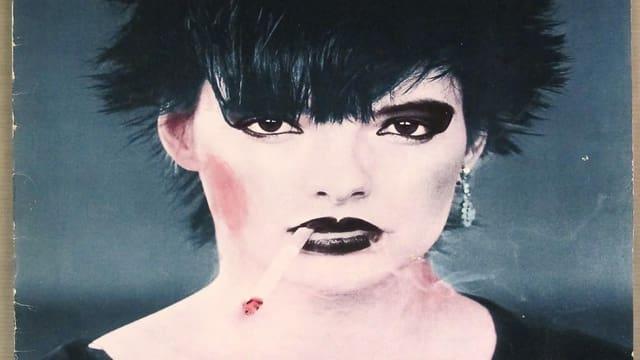 Nina Hagen mit schwarzer Stachelfrisur, schwarz umrandeten Augen, eine Zigarette zwischen den schwarz geschminkten Lippen, der Blick herausfordernd.