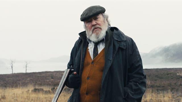 Ein alter Mann mit Bart und einem Gewehr im Arm steht auf einem nebligen Feld.
