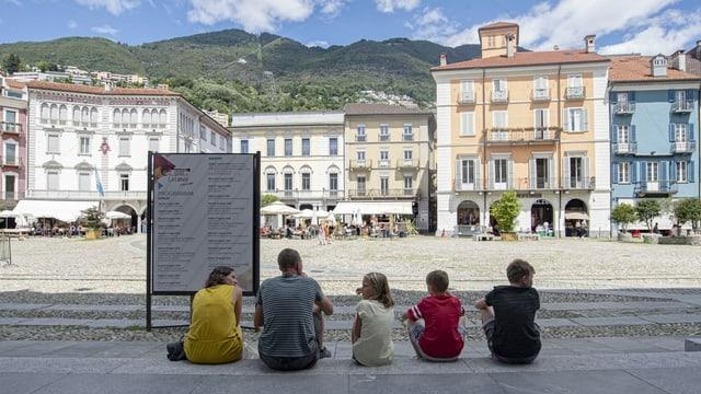 Familie mit drei Kindern sitzt am Rand der leeren Piazza Grande