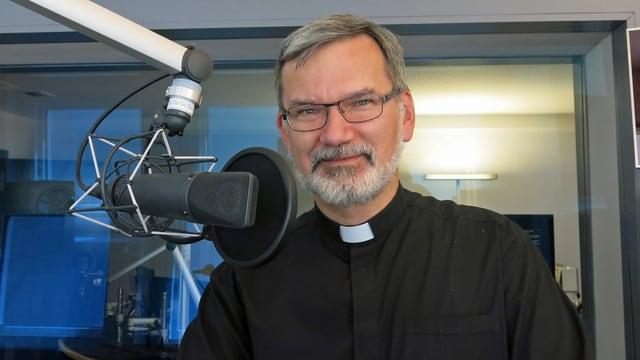 Ein Mann in Priesterhemd steht hinter dem Mikrophon.