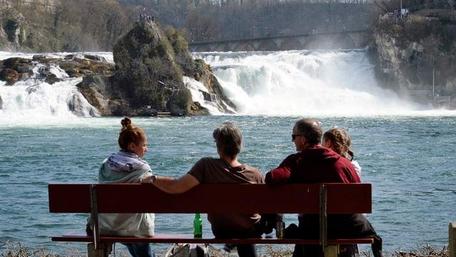 4 Personen sitzen vor dem Rheinfall auf einem Bänkli
