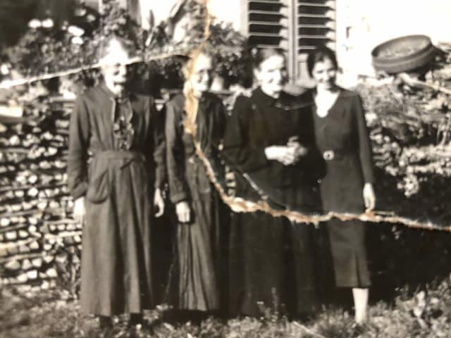 Eine schwarz-weiss Aufnahme mit vier Personen die nebeneinander stehen.