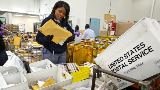 Angestellte sortiert Briefe in einem USPS-Zentrum