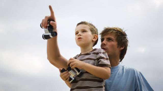 Vater und Sohn betrachten den Himmel.