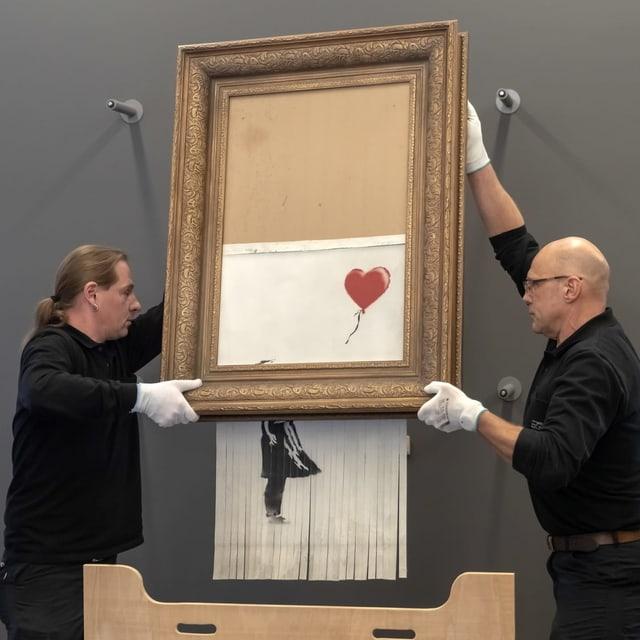 Zwei Museumsmitarbeiter hängen Banksys geschreddertes Bild auf