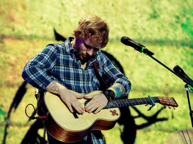 Ed Sheeran trommelt auf seiner Gitarre.