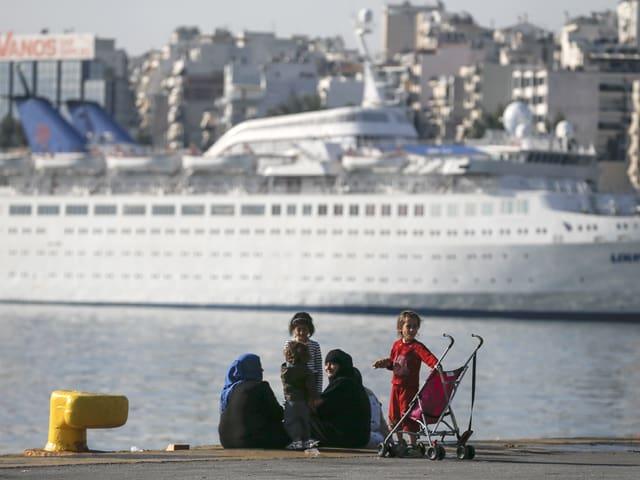 Eine Gruppe Frauen und Kinder sitzt am Pier, im Hintergrund eine Passagierfähre.