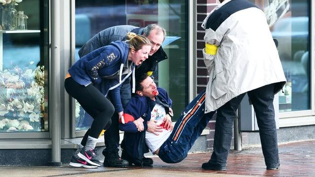Drei Menschen tragen einen stark blutenden Mann über einen Gehsteig.