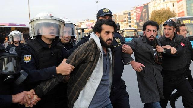 Zu sehen sind tükrische Polizisten, die einen Demonstranten abführen.