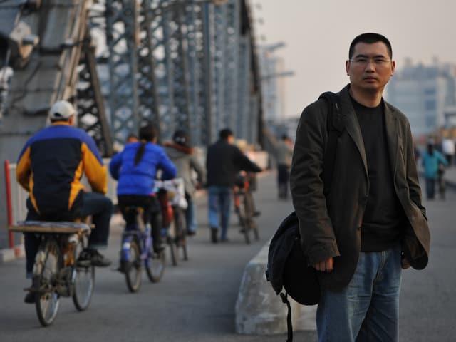 Chang Ping steht auf einer Brücke.