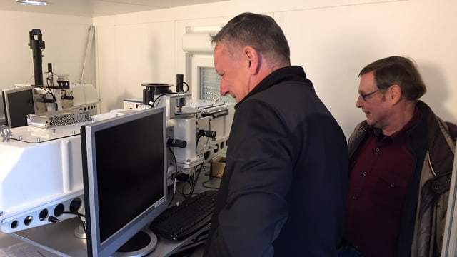 Zwei Männer stehen lächelnd vor einem Bildschirm.