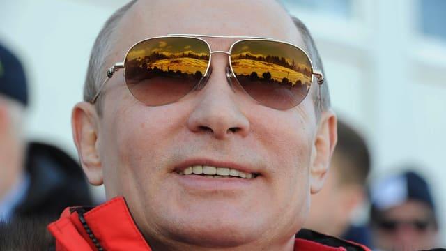 Wladimir Putin mit Sonnenbrille, in der sich die Berge von Sotschi spiegeln.