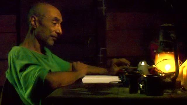 Mann sitzt an Tisch.