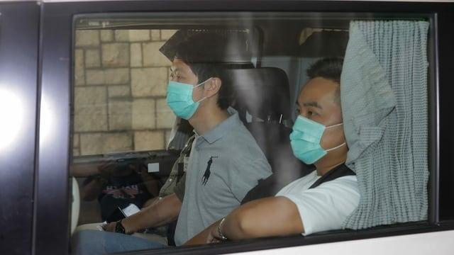 Zwei Hongkonger sitzen in einem Auto, sie tragen Hygienemasken.