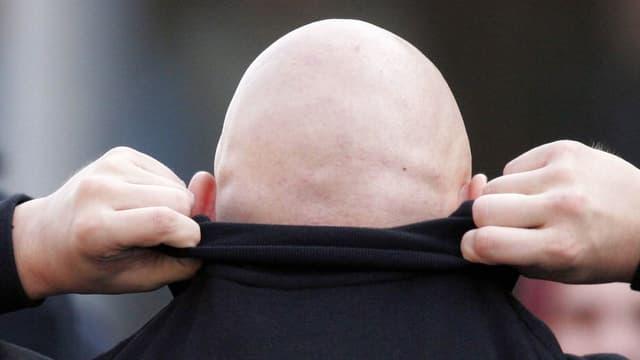 Ein Mann mit Glatze.