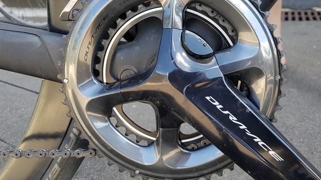 Die Kurbelachse eines Fahrrades, dahinter zwei grosse Zahnräder.
