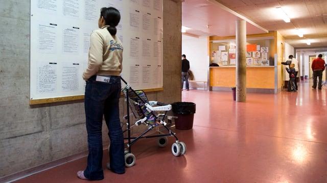 Frau mit Kinderwagen blickt an eine Wand mit einer Informationstafel.