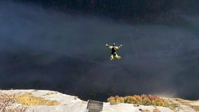 Ein Base-Jumper in einem gelben Anzug springt gerade von einer Klippe in die Tiefe.