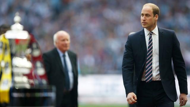 Prinz William steht auf Fussballrasen.