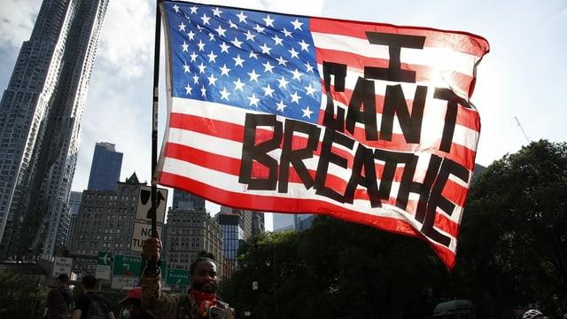 """ein Mann hält eine US-Flagge mit den Wörtern """"I can't breathe"""" auf"""