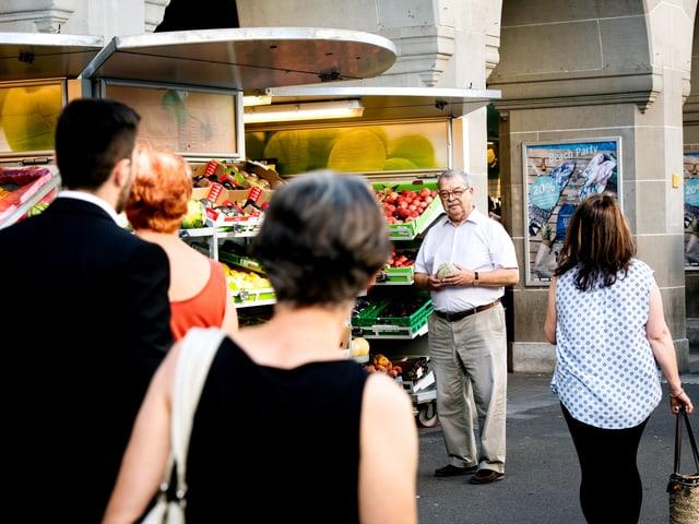 Ein Mann steht an einem Gemüsestand und Menschen ziehen an ihm vorbei.