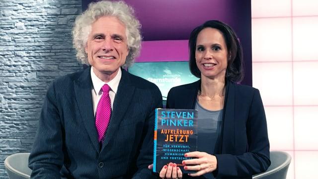 Ein Mann mit pinker Krawatte sitzt neben einer Frau, die ein Buch in der Hand hält.