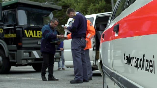 Zwei Polizisten und ein Lastwagenfahrer stehen beisammen. Die Polizisten kontrollieren Unterlagen.