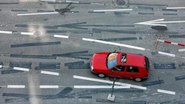 Ein rotes Auto befährt eine Kreuzung mit einem Wirrwar aus übermalten und aktuellen Leitlinien.