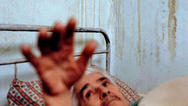 Mann liegt im Bett und streckt die Hand hoch.