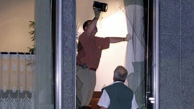 Zwei Männer untersuchen ein eingeschlagenes Fenster mit einer Lampe.
