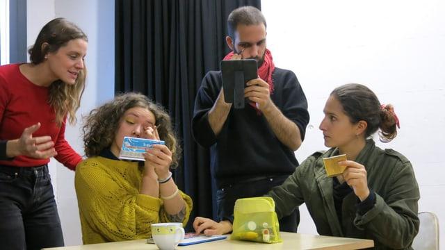 vier junge Schauspielerinnen und Schauspieler schminken sich