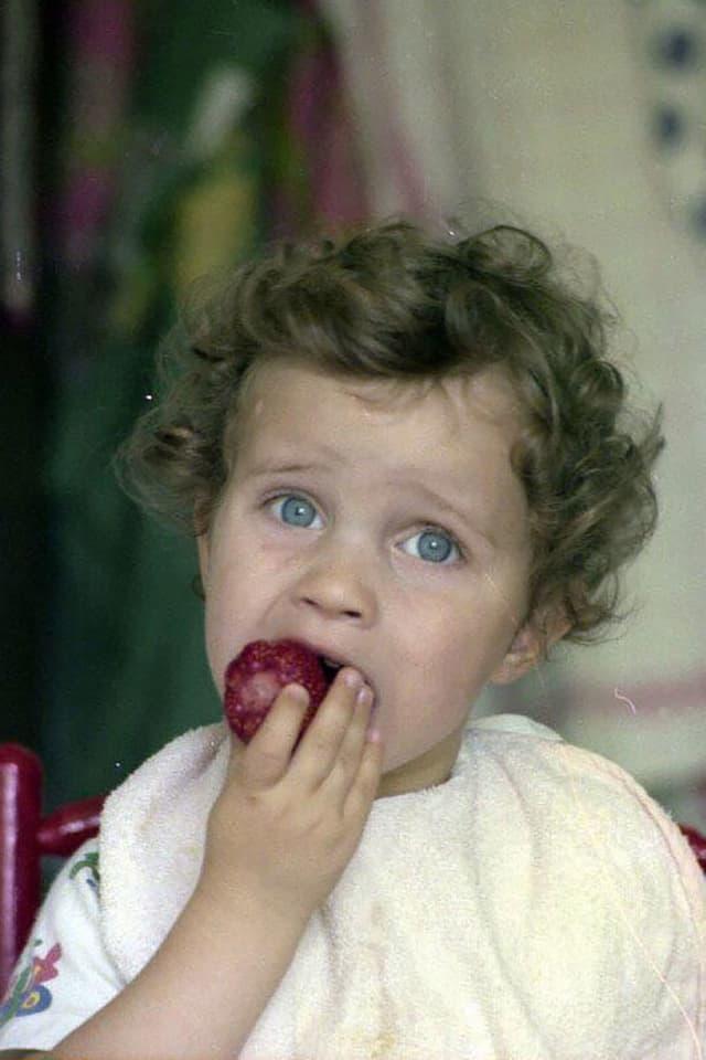 Klein Adrian Küpfer beisst in eine Erdbeere.