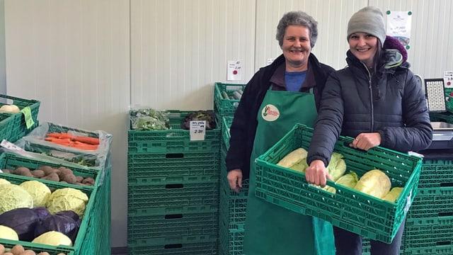 Zwei Frauen stehen zwischen Gemüsekisten