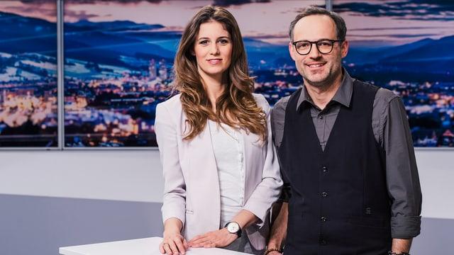 Annina Campell und Livio Foffa stehen im Studio und schauen in die Kamera.