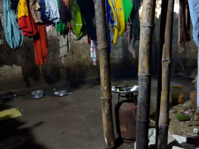 Ein Kocher mit Gasflasche steht unter trocknender Wäsche.
