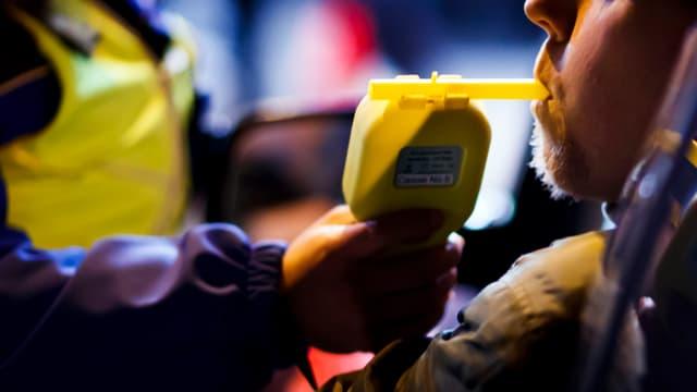 Polizist lässt Autofahrer in ein Alkoholmessgerät blasen.