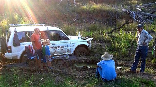 Landrover ist im schlammigen Boden eingesunken. Die Familie und zwei Retter stehen vor dem Wagen.