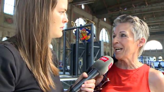 Eine junge Frau befragt mit einem Mikrofon eine ältere Dame.