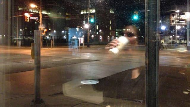 Eine leere Strassenkreuzung, in einer Scheibe die Reflexion einer jungen Frau, die Kaffee trinkt.