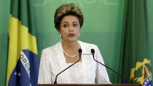 Präsidentin Rousseff steht hinter zwei Mikrophonen und spricht an einer PK.