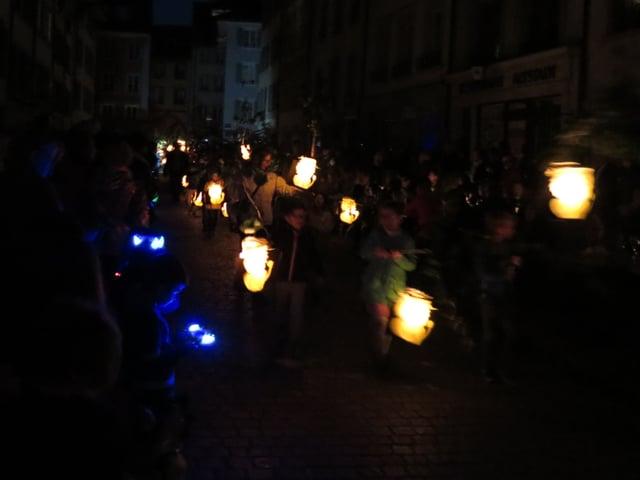Mehrere Kinder bilden einen Umzug mit Lampions