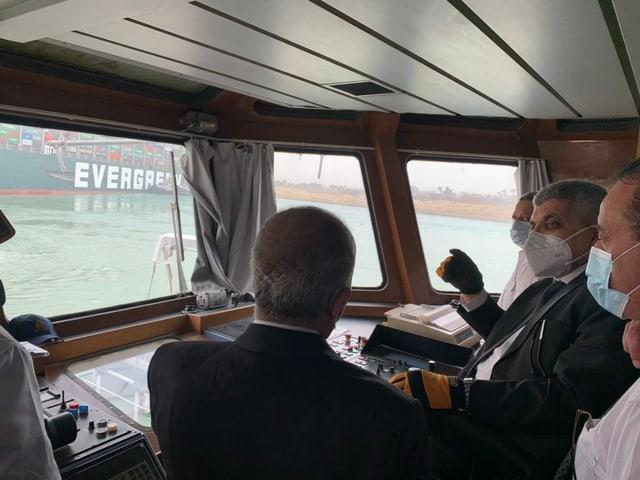 Membros da Autoridade do Canal de Suez examinam o incidente e discutem como agir. O navio porta-contêineres deve ser rebocado de volta ao corredor correto por vários rebocadores.