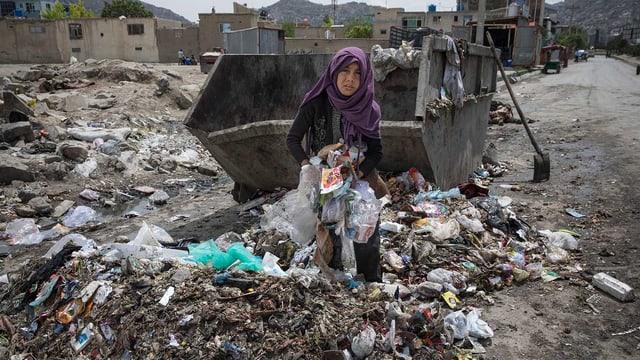 Das Mädchen durchwühlt eine Mülldeponie.