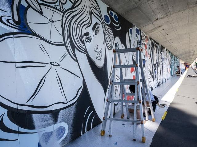 Malereien an der Schwarzwaldbrücke. Zu sehen ist eine lächelnde Frau und eine Malerin auf einer Leiter.
