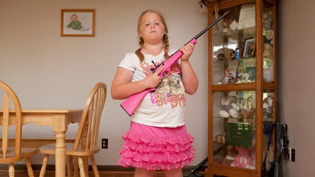Ein junges Mädchen posiert mit ihrer pinken Waffe im Esszimmer. Sie trägt ein pinkes Röckchen und pinke Flipflops.