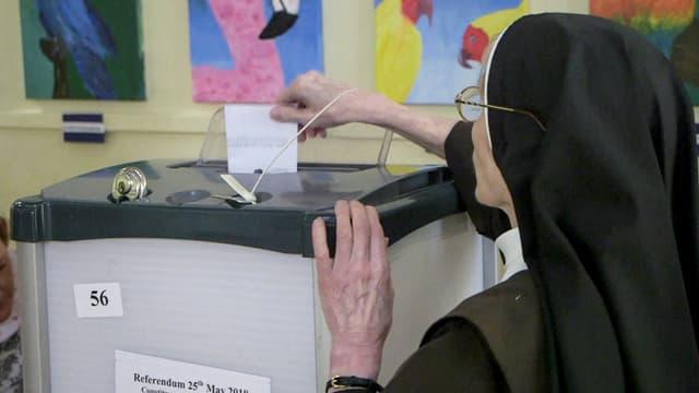 Eine Klosterfrau gibt ihre Stimme ab